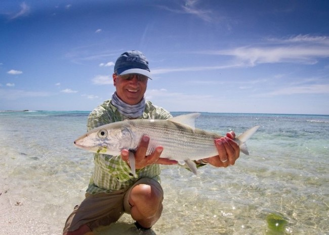 Russell in the crystal clear waters of Cozumel admiring his flats fishing catch.