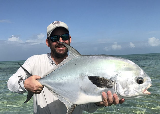 Ernesto showing off to his party the big game he caught in the fly fishing tour.