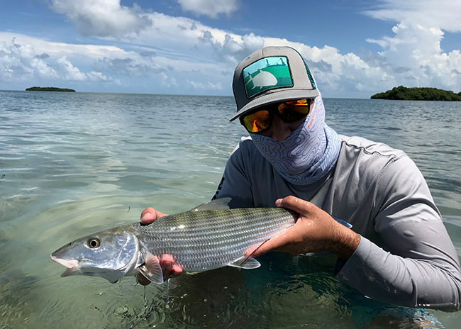 Brent is holding the fish he caught with his fly fishing party in Cozumel.